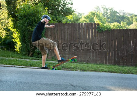 Action shot of a longboarder skating on an urban road. - stock photo