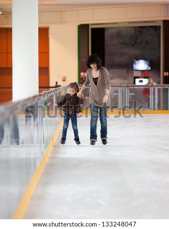 Action shot of beautiful woman teaching her daughter how to ice skate - stock photo