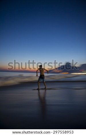 Action silhouette of Brazilian riding skimboard on Ipanema Beach Rio de Janeiro Brazil at sunset - stock photo