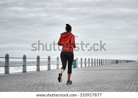 Active adult woman busy taking a morning run on the promenade along the ocean side with a dramatic sky - stock photo