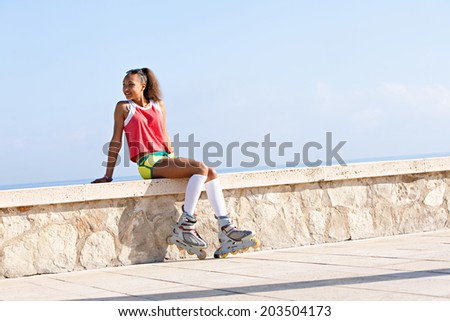 Active african american black teenager girl sitting with her roller skates by the beach, smiling during a summer sunny day on holiday, outdoors. Attractive joyful girl against a blue sky. - stock photo
