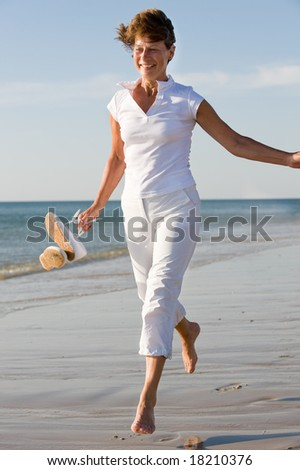 Active and happy senior woman running at the beach - stock photo