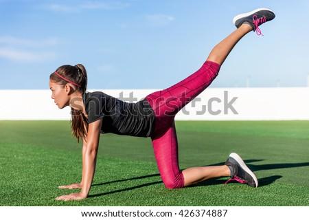 Active Asian young adult doing bodyweight glute and leg exercises on outdoor grass. Fitness woman doing donkey kick exercise for glutes strength training, butt toning and body core health. - stock photo