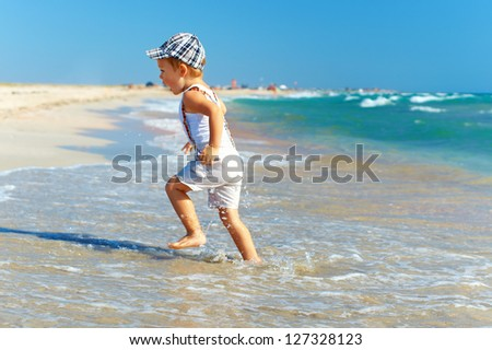active baby boy having fun in surf on the beach - stock photo