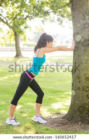 Active beautiful brunette stretching her leg in a park on a sunny day - stock photo