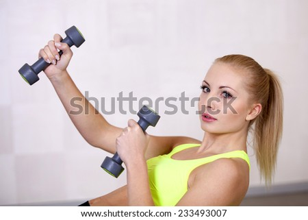 Active beautiful sports girl lifting dumbbells doing workout in a fitness club or gym - stock photo