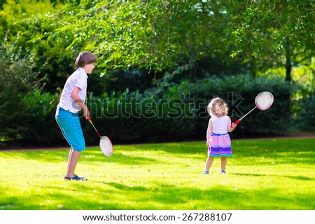 Active children playing badminton. Two happy kids, boy and girl having fun on a family picnic in a park, enjoying sport games, running and jumping with tennis racket on a hot summer day outdoors. - stock photo
