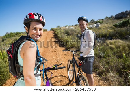 Active couple cycling on country terrain together on a sunny day - stock photo