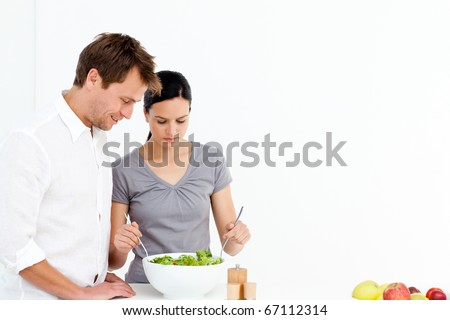 Active couple preparing a salad for lunch in the kitchen - stock photo