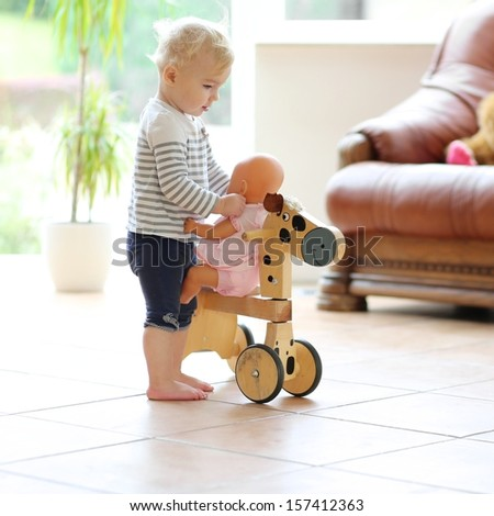Active cute little baby girl plays with doll and wooden wheeled horse, standing barefoot on tiles floor inside a house in front of a big window - stock photo