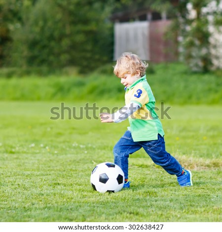 Active cute little kid boy playing soccer and football and having fun, outdoors on field. Active leisure with children on warm sunny summer day. - stock photo