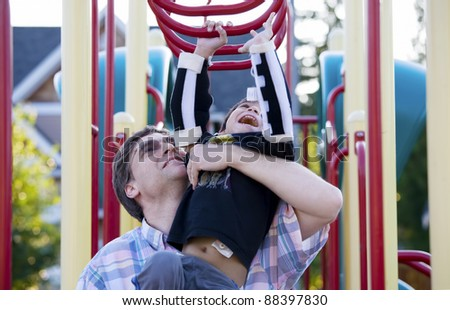 Active disabled five year old boy playing on the  monkey bars with his father - stock photo