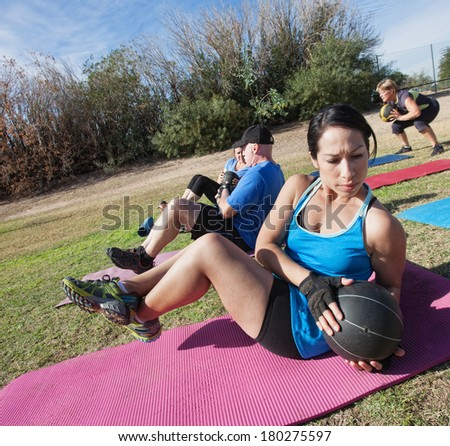 Active diverse group in boot camp fitness class on mats - stock photo