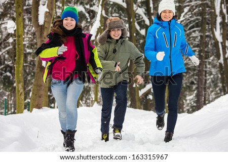 Active family - mother and kids running, jumping in winter park - stock photo