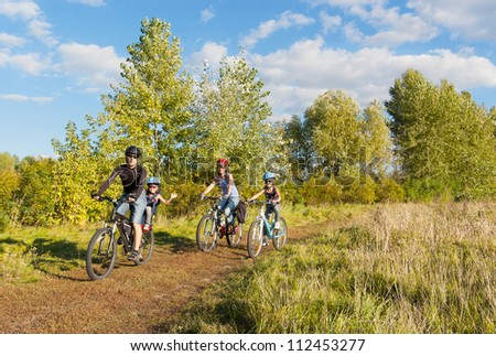 Active family on bikes cycling outdoors. Happy parents with two kids on bicycles. Sport and healthy lifestyle with children, family summer vacation - stock photo