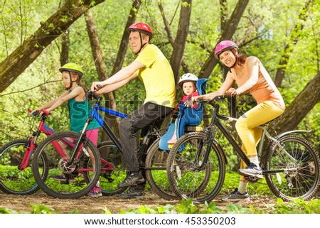 Active family on bikes riding in sunny forest - stock photo
