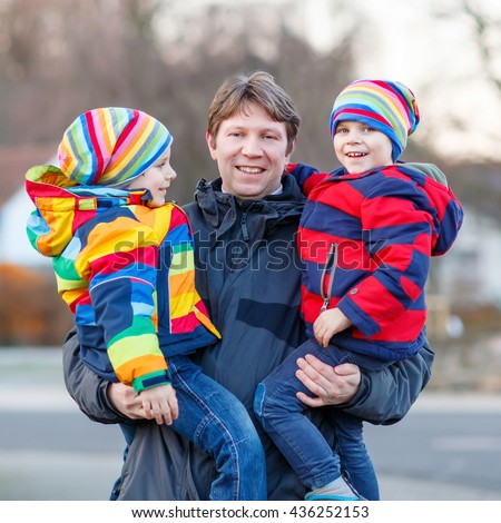 Active father holding his children, little funny kids boys on arm, on cold day. Man and boys walking together in a park in spring, autumn or winter. Happy, joyful family - stock photo