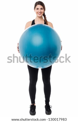 Active female gym instructor displaying a swiss ball. - stock photo