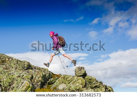 Active female hiker have fun in rocky mountains - stock photo