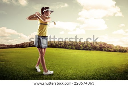 Active female player preparing for hitting golf ball. Young sporty girl looking at ball course on green field. - stock photo