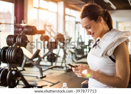 Active girl with smartphone listening to music in gym. - stock photo