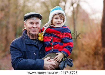 Active grandfather holding his grandchild, little toddler boy on arm, on cold day, walking together in a park in spring, autumn or winter. Happy, joyful family. - stock photo