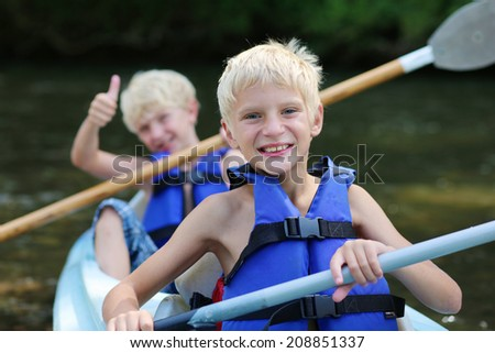 Active happy twin brothers, teenage school boys, having fun together enjoying adventurous experience kayaking on the river on a sunny day during summer vacation - stock photo