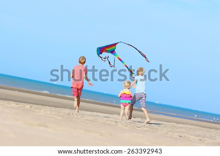 Active healthy children, teenager brothers with cute toddler sister playing together on the beach flying colorful kite - happy carefree childhood concept - stock photo