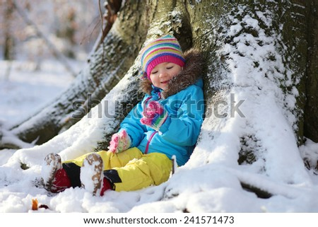 Active healthy toddler girl wearing colorful snowsuit and bright knitted hat and mittens enjoying snow playing in a beautiful snowy forest on sunny winter day - stock photo