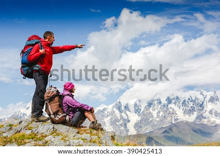 active hikers hiking enjoying view looking at mountain landscape - stock photo