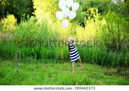 Active kid girl in stripe dress has fun with white balloons outdoor on the beauty summer day: runs and jumps - stock photo