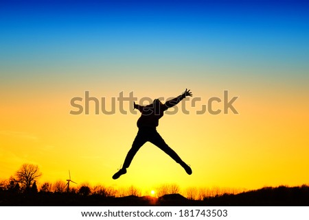 Active kid jump in meadow at sunset - stock photo