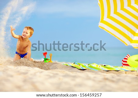 active kid playing in sand on the beach - stock photo