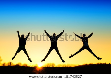 Active kids jump in meadow at sunset - stock photo