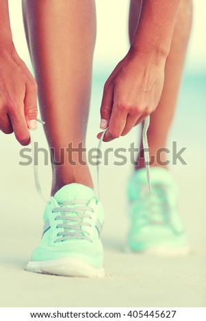 Active life runner girl tying running shoes laces. Healthy lifestyle woman runner tying running shoes laces for cardio training on beach at sunset. Female athlete exercising. - stock photo