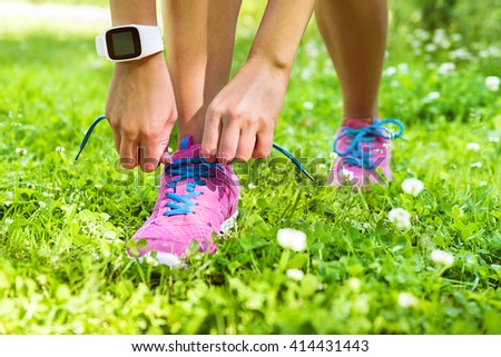 Active lifestyle smartwatch runner woman tying running shoes. Healthy summer living. Sports girl getting ready for weight loss run exercise lacing footwear laces wearing activity tracker wristwatch. - stock photo
