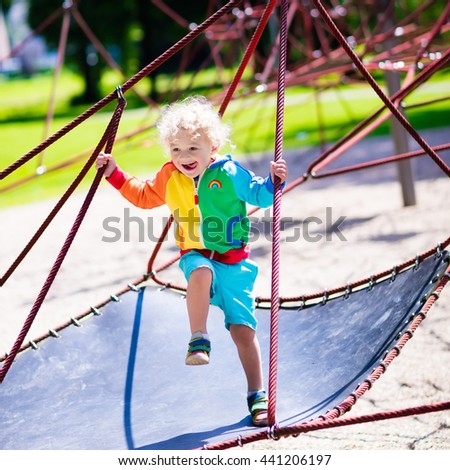 Active little child playing on climbing net and jumping on trampoline at school yard playground.  - stock photo