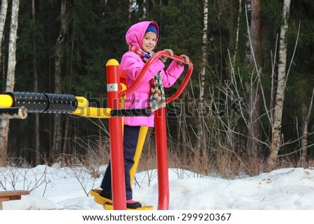 Active little girl at playground in winter outdoor Zelenograd, Moscow, Russia - stock photo