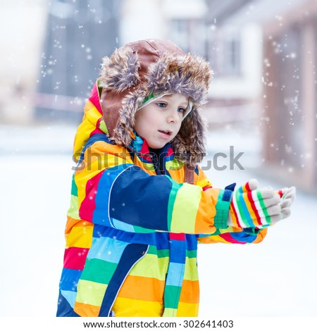 Active little preschool boy in colorful winter clothes having fun with snow, catching snowflakes, outdoors during snowfall on cold day. Active outdoors leisure with children in winter. - stock photo