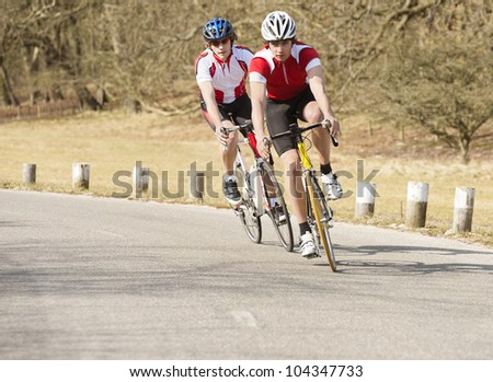 Active male bike riders riding cycles on a country road - stock photo