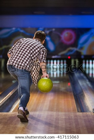 Active man playing bowling indoors - stock photo