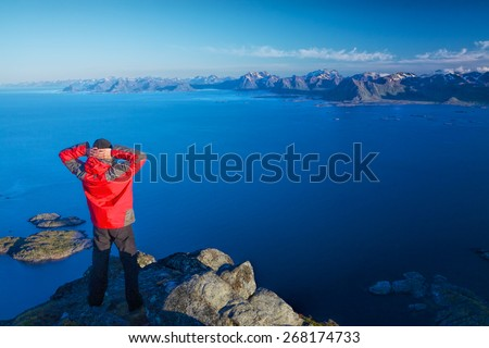 Active man standing on the top of mountain Festvagtinden viewing picturesque scenery of Lofoten islands, Norway - stock photo