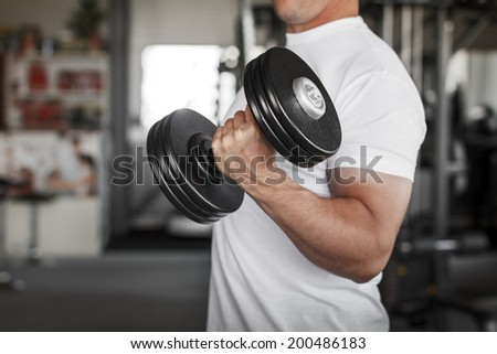 Active man workout, exercise with dumbbell in gym - stock photo