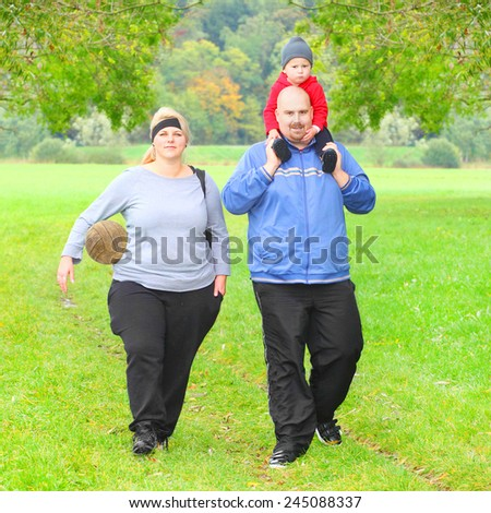 Active parents with her son walking together on green meadows. - stock photo