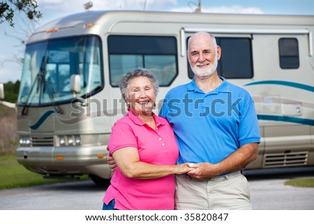 Active retired couple in love with their luxury motor home in background. - stock photo