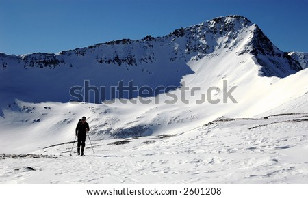 active retired man ski touring in the rocky mountains - stock photo