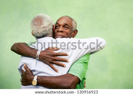 Active retired old men and leisure, two senior black brothers hugging outdoors - stock photo