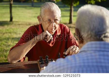 Active retired people, old friends and free time, two senior men having fun and playing chess at park. Head and shoulders - stock photo