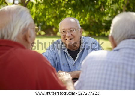Active retired senior people, old friends and leisure, group of four elderly men having fun, laughing and talking in city park. Waist up - stock photo