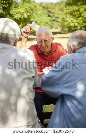 Active retirement, old people and seniors free time, group of three elderly men having fun and playing cards game at park. Waist up - stock photo